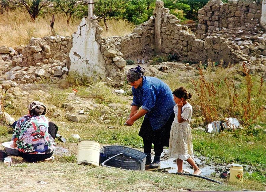 Женщина стирает вещи у разрушенного села в Ботлихском районе Дагестана